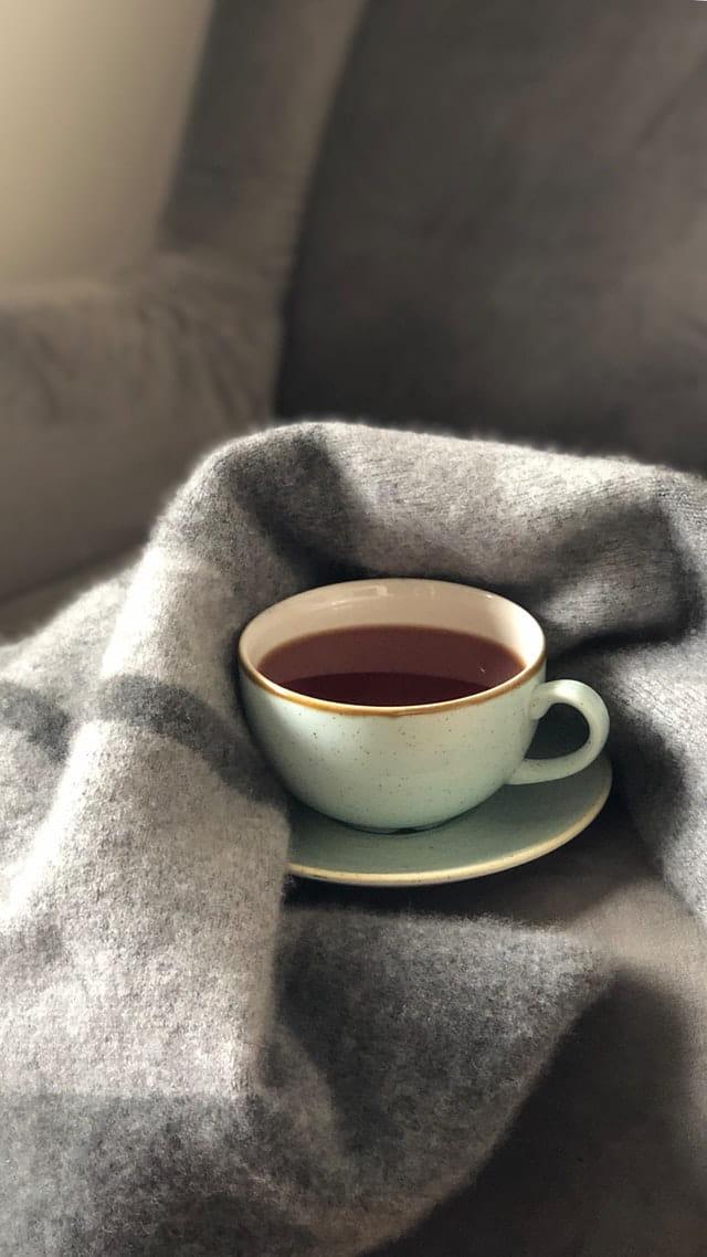 Tasse de thé chaud sur un plaid.