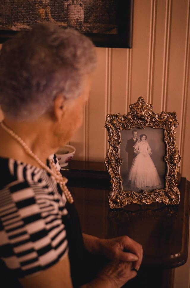 Personne âgée qui regarde sa photo de mariage.