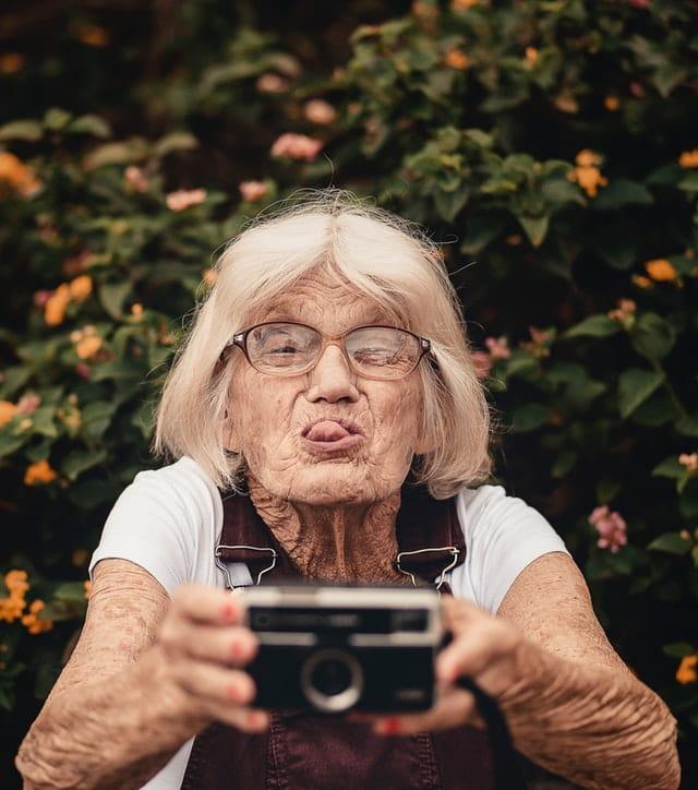 Dame âgée qui s'amuse en faisant la grimace.