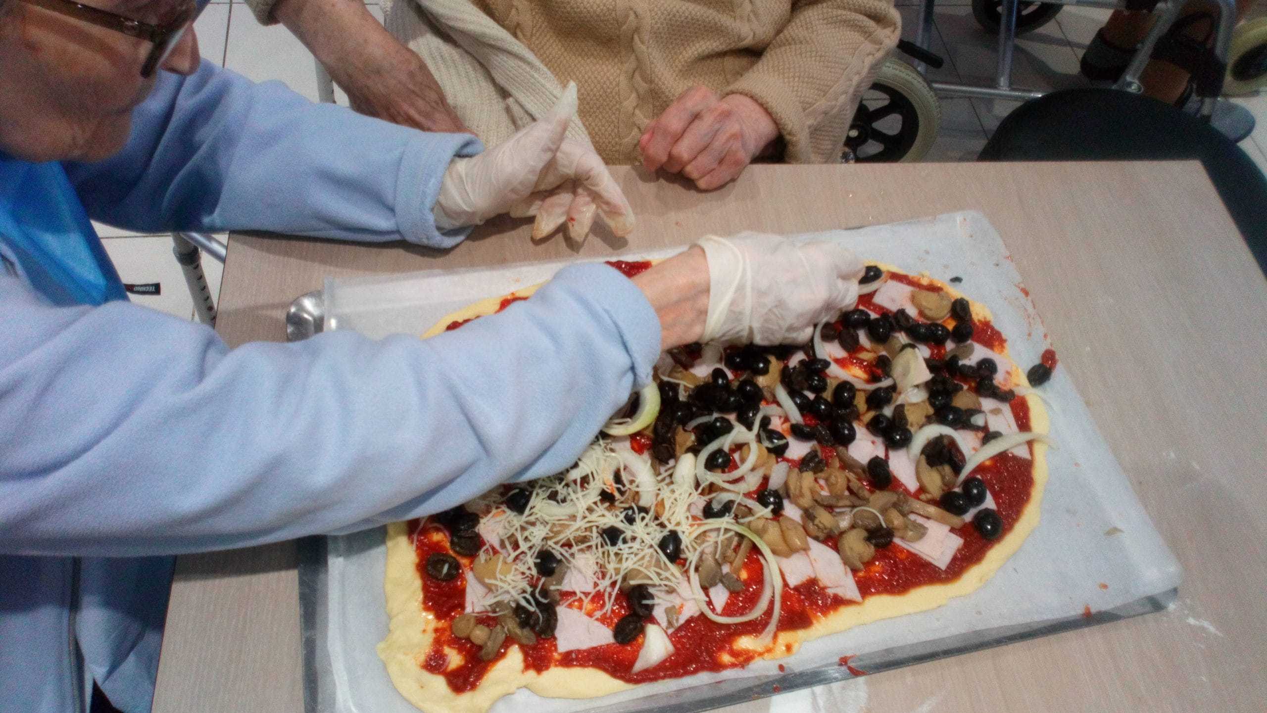 Finition de la pizza à l'atelier de la maison de retraite.