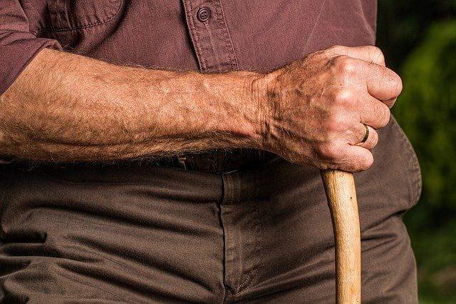 Une personne âgée en maison de retraite avec un bâton.