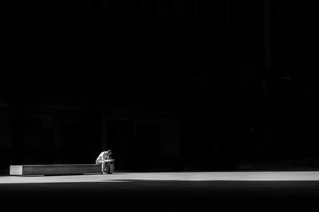 Une personne âgée assise seule.