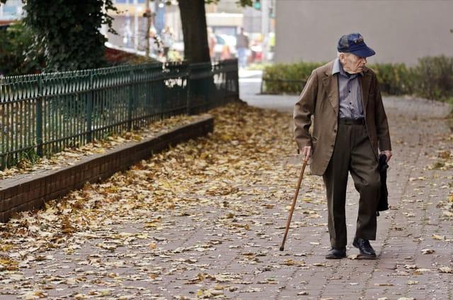 Personne âgée qui marche avec une canne devant sa maison de retraite.
