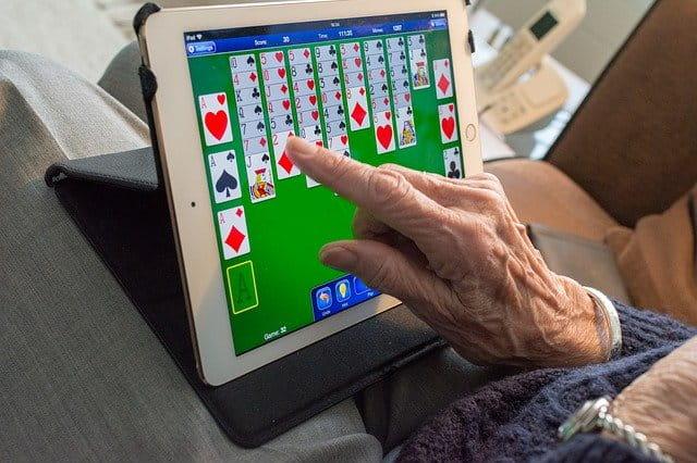 Personne âgée jouant au solitaire sur une tablette tactile.