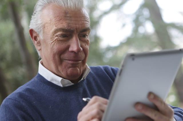 Homme âgé qui utilise une tablette tactile.