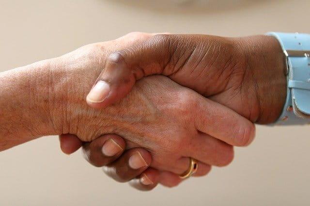 Une personne âgée qui sert la main de son infirimière.