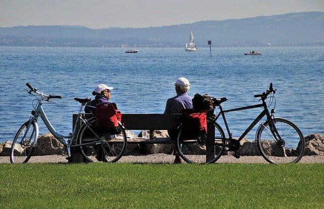 Personnes âgées assises sur un banc avec leurs vélos