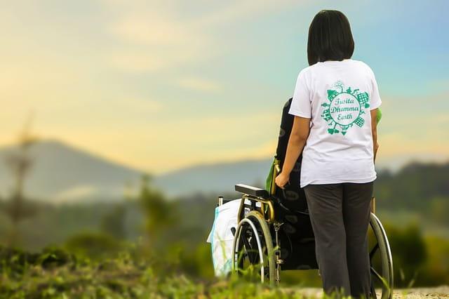 Personne poussant un fauteuil roulant de dos.