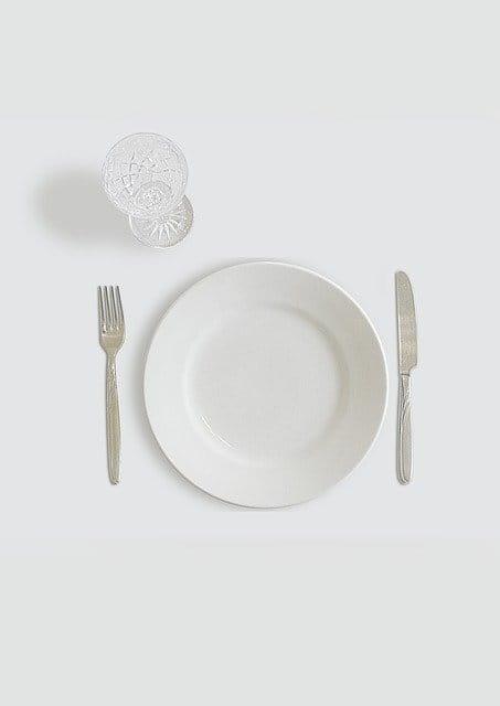 Assiette vide et couverts sur une nappe blanche