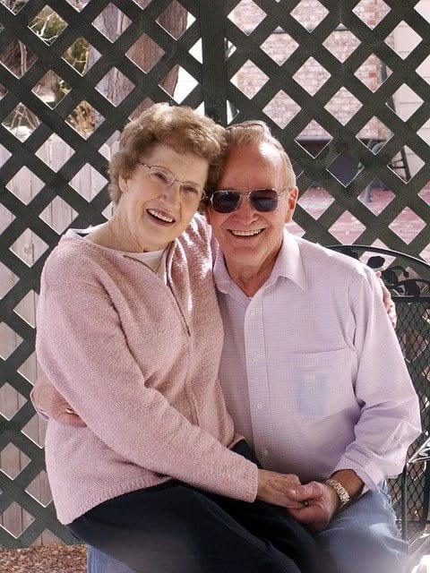 Couple de personnes âgées avec de grands sourires.
