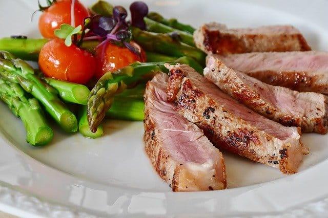 assiette avec de la viande, des asperges et des tomates