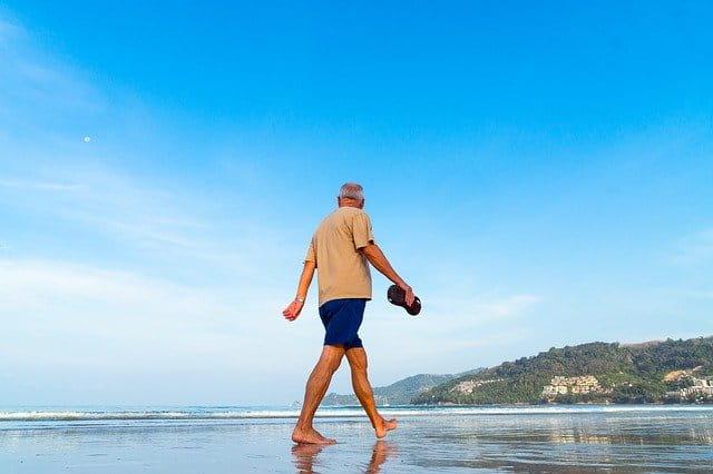 Personne âgée marchant sur la plage.