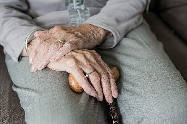 Mains d'une femme âgée tenant une canne.