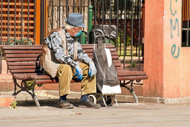 Personne âgée assise sur un banc avec un masque