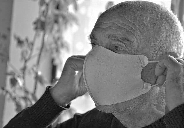 Une personne âgée portant un masque.