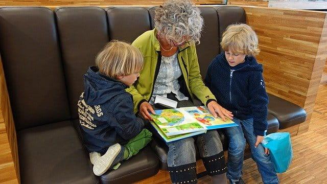 Grand-mère lisant un livre à ses petits-enfants.