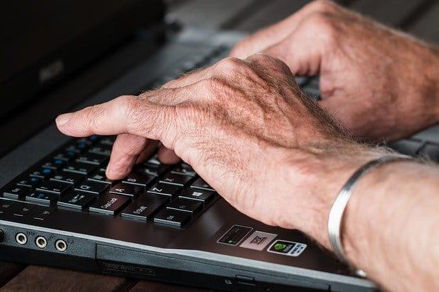 Mains de personne âgée qui dactylographient.