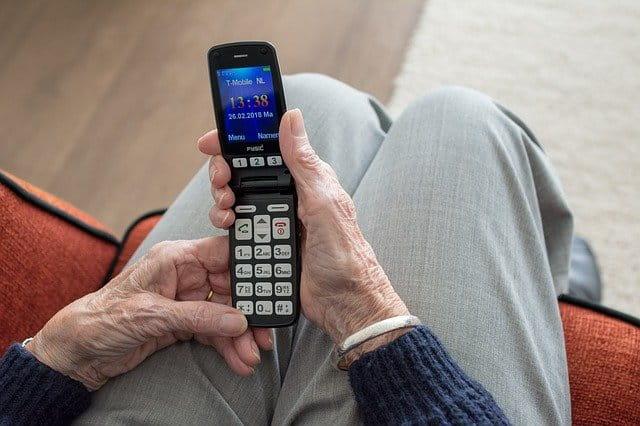 Femme âgée tenant un téléphone portable.