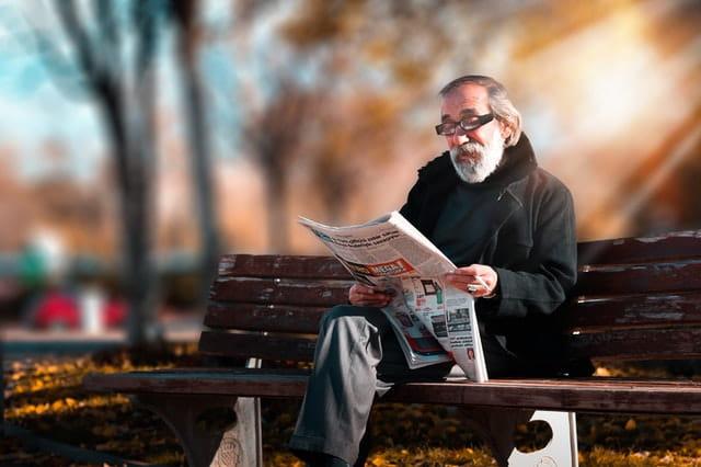 Personne âgée lisant le journal sur un banc.