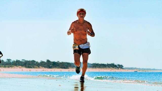 Personne âgée qui court sur la plage.