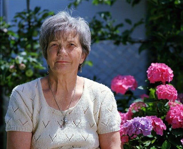 Dame âgée se reposant dans un jardin.