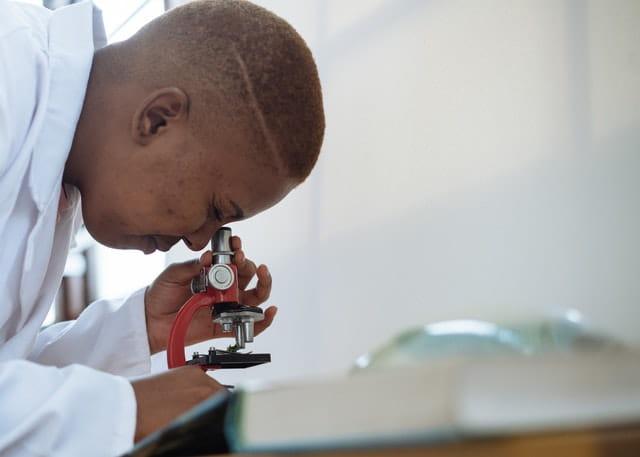 Médecin en train de regarder au microscope.