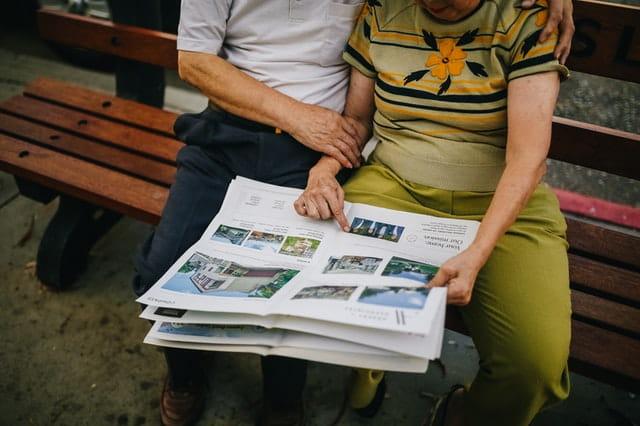 Personnes âgées lisant un journal.