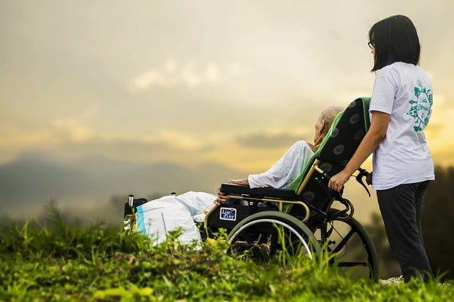 Une jeune personne qui pousse une personne âgée en fauteuil roulant.